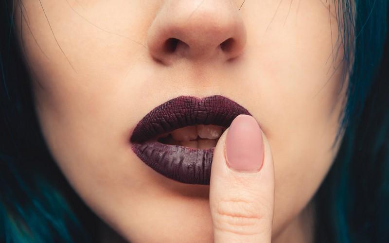 Девушка прикасается пальцем к левому уголку губы