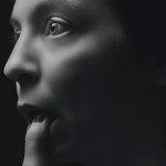 Женщина касается пальцем нижней губы