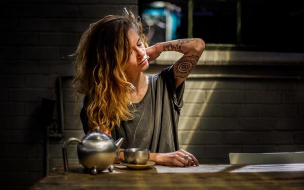 Девушка сидит за столом и чешет шею сзади