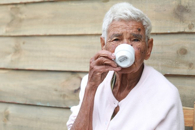 Мужчина с родинками на лице пьет из чашки