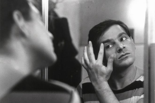 Мужчина рассматривает в зеркало прыщик возле левого глаза