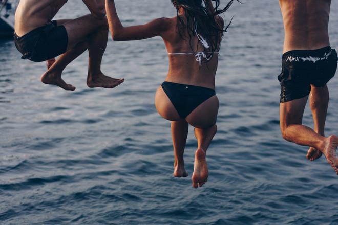 Девушка и парни прыгают в воду
