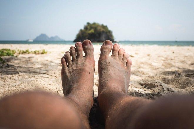 Родинка на ноге у отдыхающего на пляже