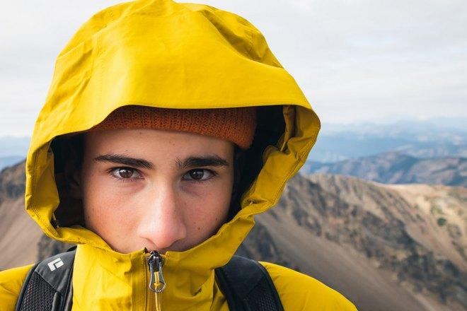 Парень в желтой куртке на фоне гор
