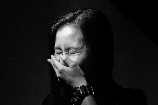 Девушка чихает, прикрывая рот левой рукой