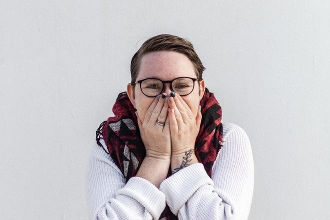 Женщина в очках прикрыла рот руками