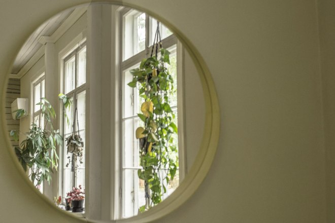 Круглое зеркало напротив окна