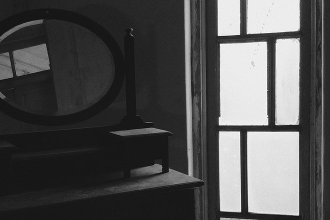 Овальное зеркало возле окна