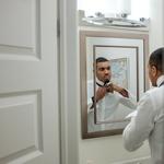 Мужчина завязывает галстук перед зеркалом