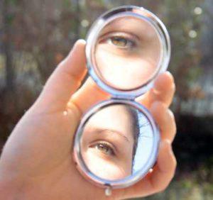 смотрит в зеркале