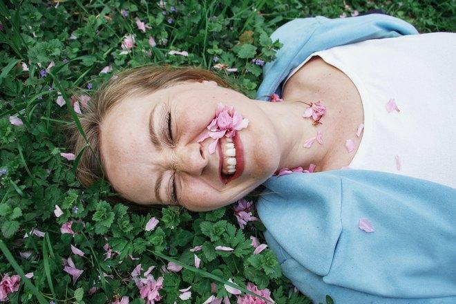 Девушка лежит в цветах и улыбается