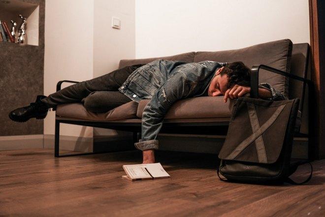 Парень спит на диване в одежде