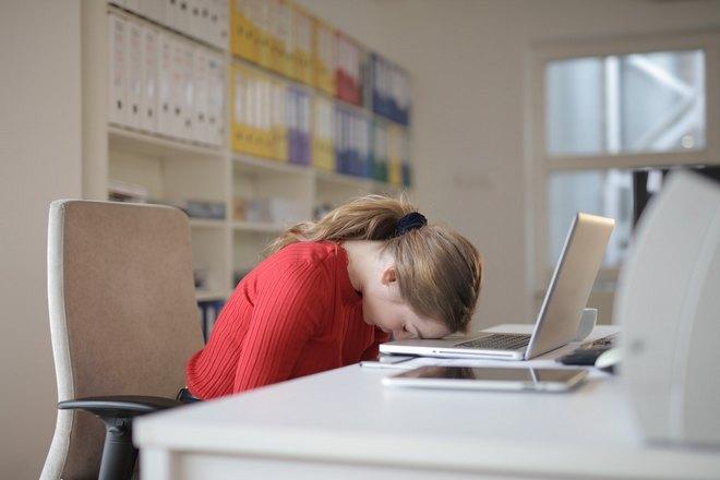 Девушка в красном спит на ноутбуке