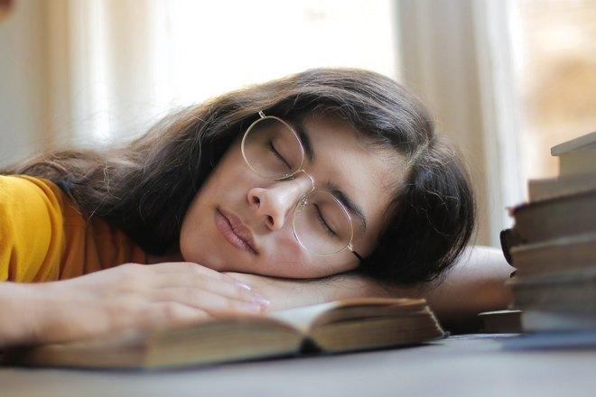 Девушка в очках спит на книге