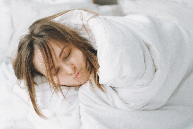 Девушка спит под теплым одеялом