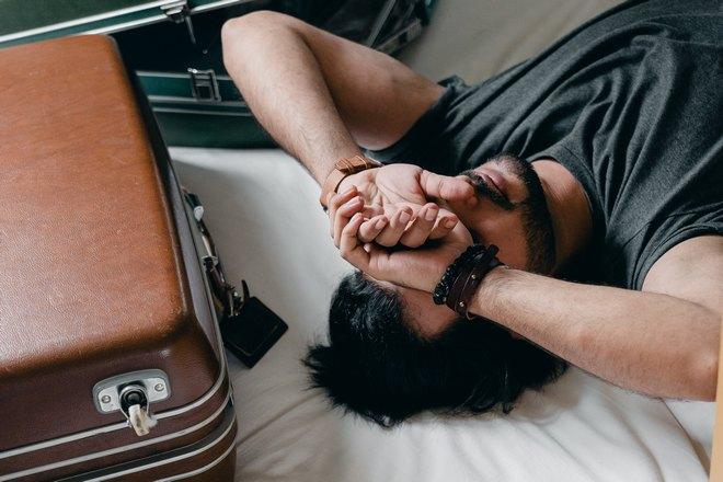 Бородатый мужчина спит возле чемодана