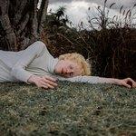 Светловолосый парень спит на траве