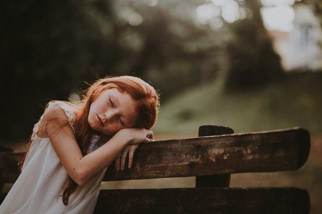 Девочка спит на скамейке