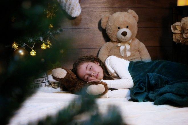 Девочка спит возле елки и мягкого медведя
