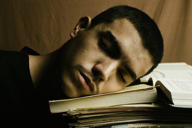 парень спит над учебниками