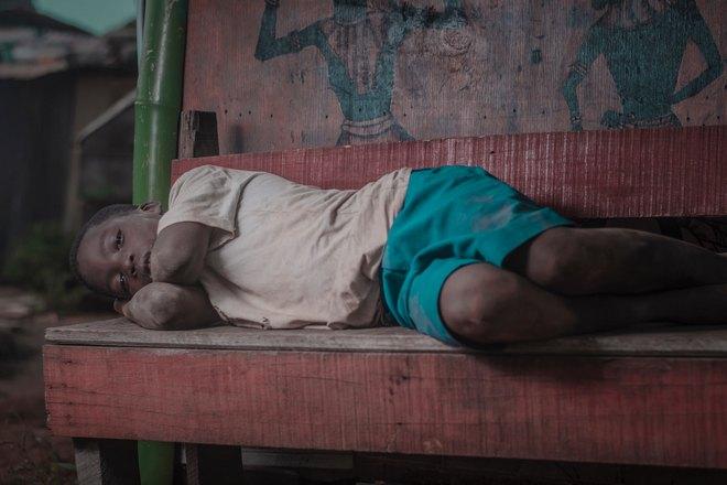 темнокожий мальчик спит на лавке
