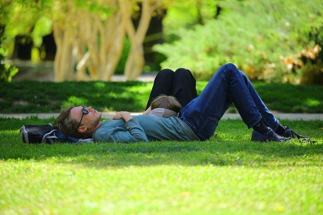 Мужчина спит на ярко-зеленой траве