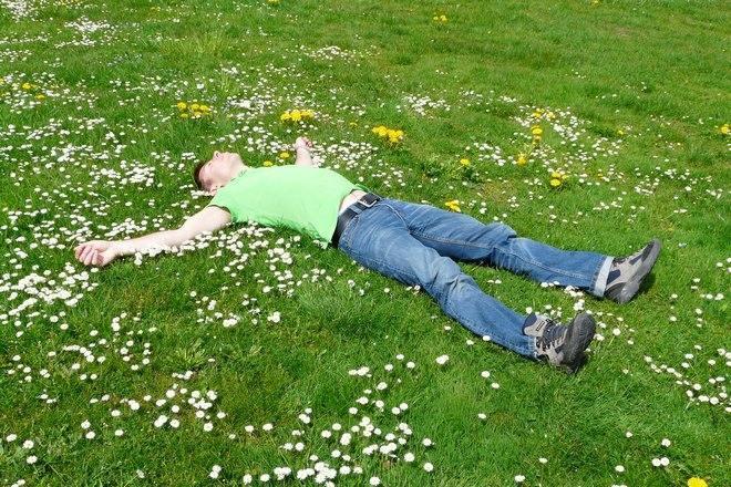 Парень спит на зеленой лужайке