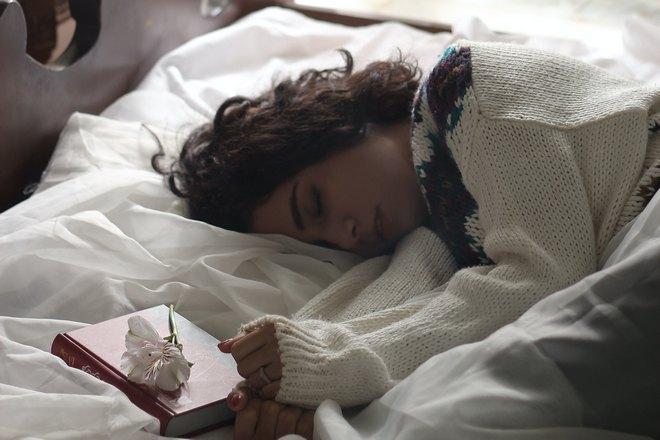 девушка спит возле книги