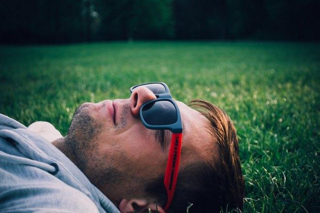 Парень в очках спит на траве
