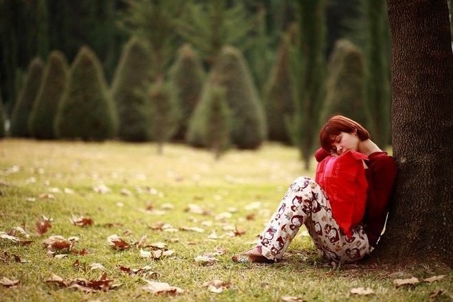 Девушка спит под деревом с красной подушкой