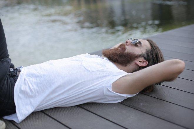 Бородатый мужчина спит на причале