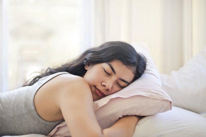 Девушка в сером спит, обняв подушку