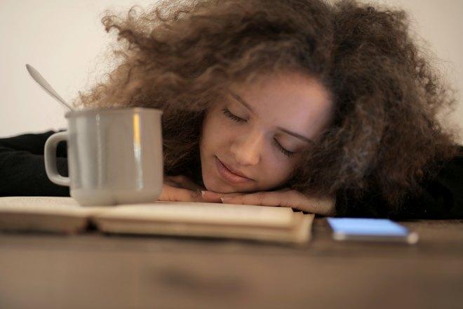 Девушка спит возле книжки и чашки