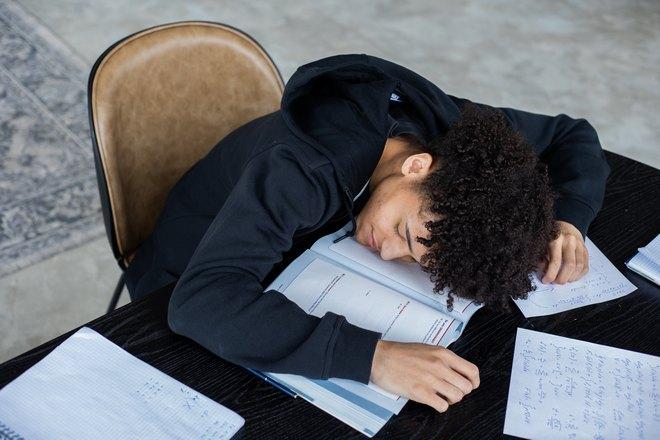 Парень уснул, сидя за столом
