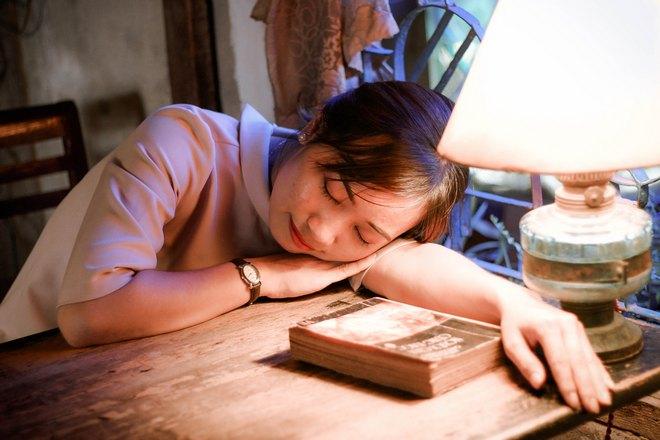 Девушка спит на столе возле ночника