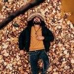 Мужчина в куртке спит на листьях