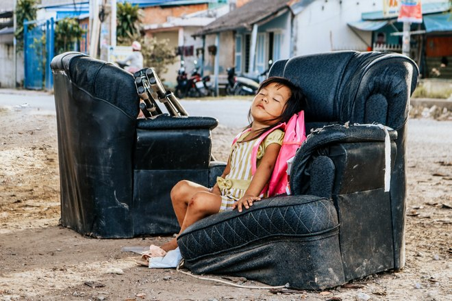 Девочка спит на уличном кресле
