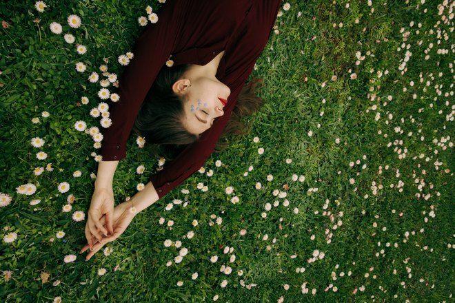 Девушка в бордовом спит на зеленой лужайке