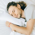 Спящий парень с красной нитью на запястье