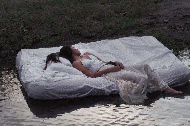 Девушка в белом спит возле воды