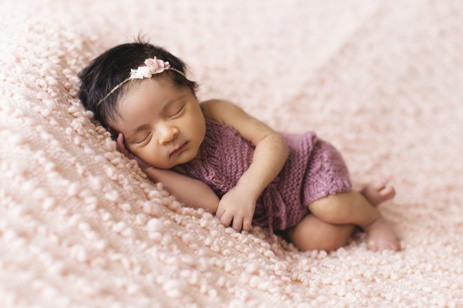 Маленькая девочка спит на мягком покрывале