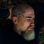 Спящий мужчина с татуировками на голове