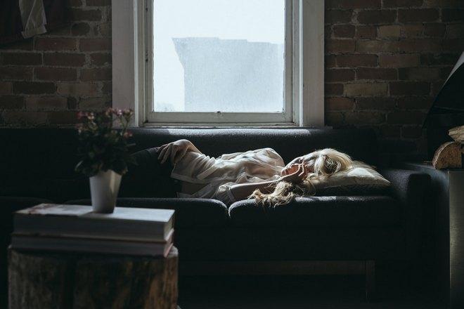 Девушка спит возле окна