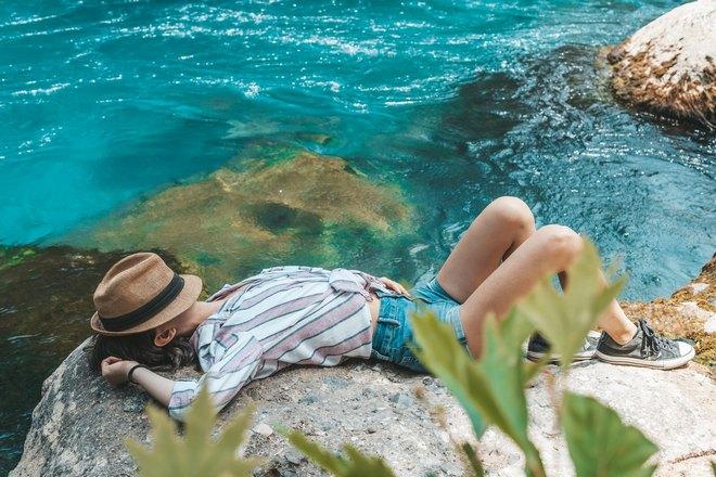 Девушка спит на камне возле моря