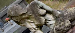 статуя лежит рядом с надгробием