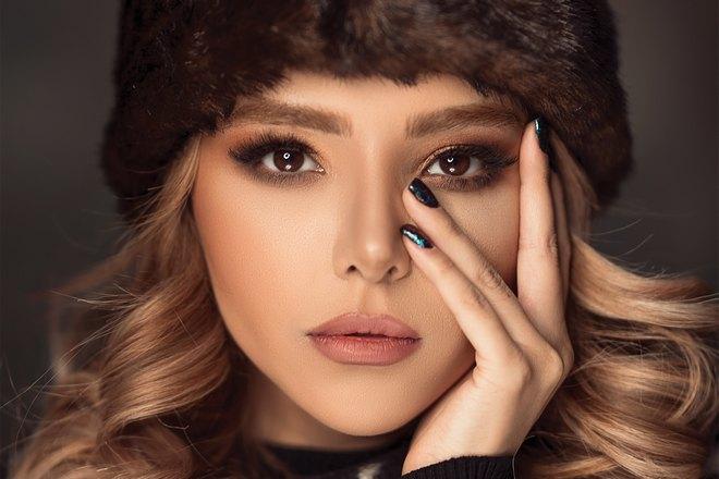 Девушка в зимней шапке прикоснулась пальцем к брови