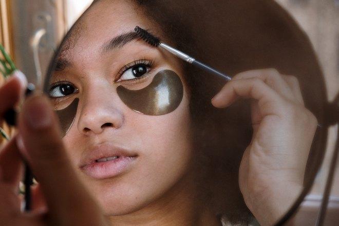 Девушка наносит макияж на бровь