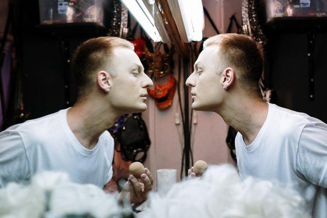 Парень в белой футболке рассматривает себя в зеркале