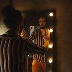 Мужчина в очках напротив зеркала