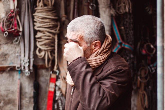 Мужчина чешет бровь левой рукой
